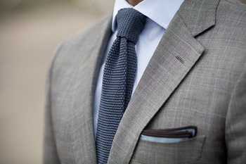 Executive execution. Grey suit. Knit tie. Piped