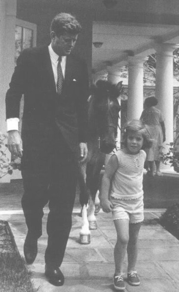 President Kennedy with his daughter Caroline as she leads her pony Macaroni away from the White House
