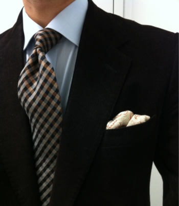 Black jacket, light blue shirt, plaid tie
